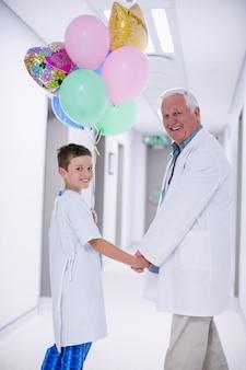 Doktor, der mit patient im krankenhauskorridor geht