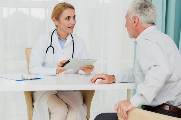 Doktor, der mit patienten beim halten der tablette spricht