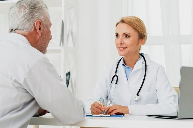 Doktor, der mit patienten sich bespricht