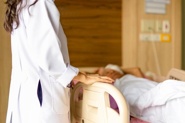 Doktor, der mit patienten während patienten im bett am krankenhaus sich bespricht.