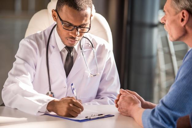 Doktor, der mit seinem männlichen patienten spricht.