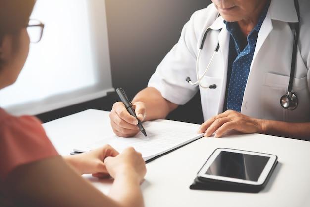 Doktor, der mit weiblichem patienten sich bespricht.