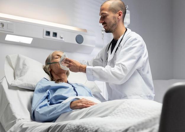Doktor, der mittleren schuss der sauerstoffmaske aufsetzt