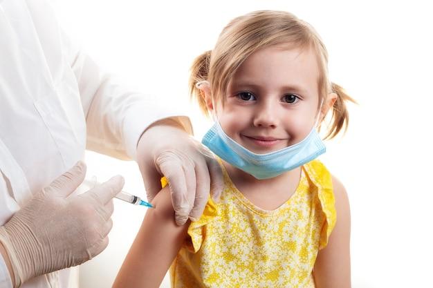 Doktor, der niedliches lächelndes kleines mädchen impft, das gelbes kleid und gesichtsschutzmaske trägt