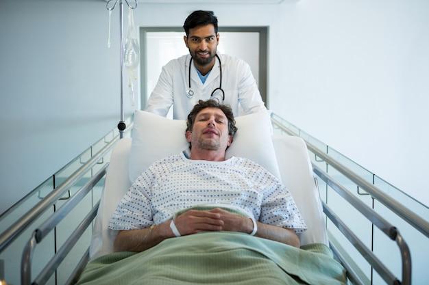 Doktor, der notfalltragebett im korridor drückt
