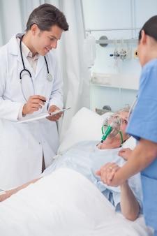 Doktor, der patienten nahe bei einer krankenschwester betrachtet