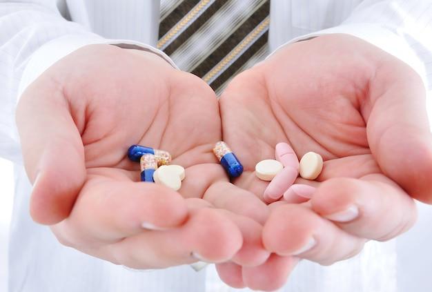 Doktor, der pillen auf seiner palme hält