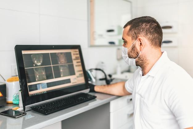 Doktor, der prüfung des röntgenstrahls macht und behandlung in der zahnmedizinischen klinik wählt