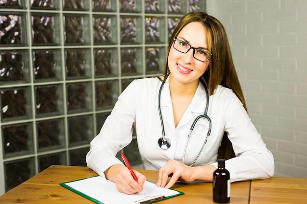Doktor, der rezept schreibt und flasche mit pillen hält