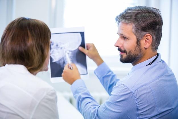Doktor, der röntgen mit patienten