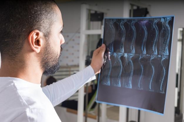 Doktor, der röntgenbild der wirbelsäule analysiert