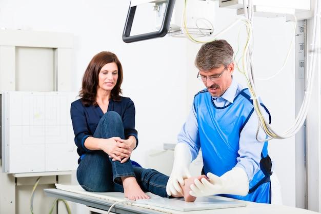 Doktor, der röntgenstrahl vom geduldigen bein in der chirurgie macht