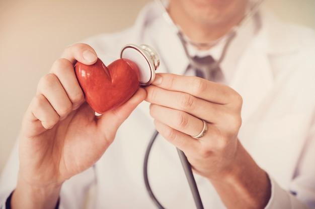 Doktor, der rotes herz, herzkrankenversicherungskonzept hält