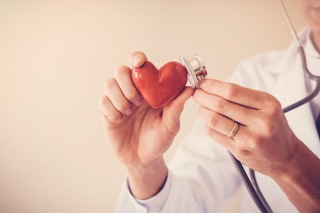 Doktor, der rotes herz mit stethoskop, herzgesundheit, krankenversicherungskonzept hält