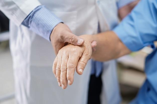 Doktor, der rührenden handasiatischen älteren frauenpatienten mit liebe und sorgfalt hält.