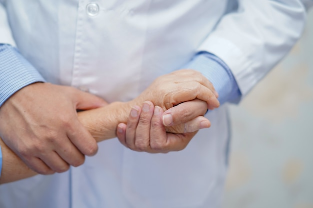Doktor, der rührenden handasiatischen älteren oder älteren frauenpatienten alter dame mit liebe, sorgfalt, helfen, ermutigen und empathie an der krankenstation hält: gesundes starkes medizinisches konzept