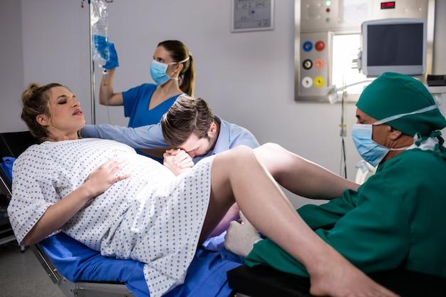 Doktor, der schwangere frau während der entbindung untersucht, während mann ihre hand im operationssaal hält