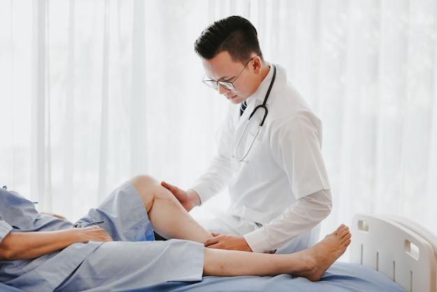 Doktor, der sein geduldiges knie auf dem bett im krankenhaus überprüft