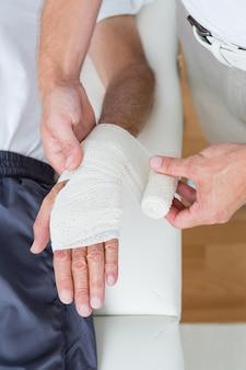Doktor, der seine geduldige hand verbindet