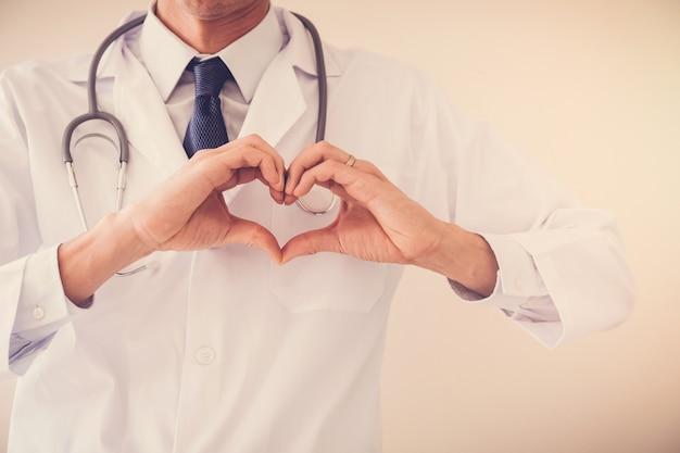 Doktor, der seine hände in der herzform, herzgesundheit, krankenversicherungskonzept macht