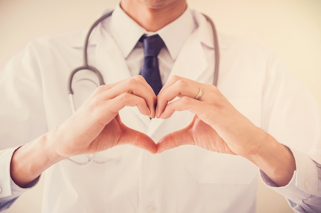Doktor, der seine hände in der herzform, herzgesundheitsversicherungskonzept macht