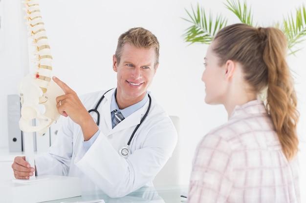 Doktor, der seinem patienten anatomische wirbelsäule erklärt