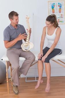Doktor, der seinem patienten anatomischen dorn zeigt