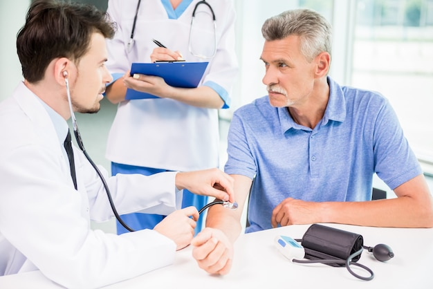 Doktor, der seinen reifen patienten mit stethoskop überprüft.