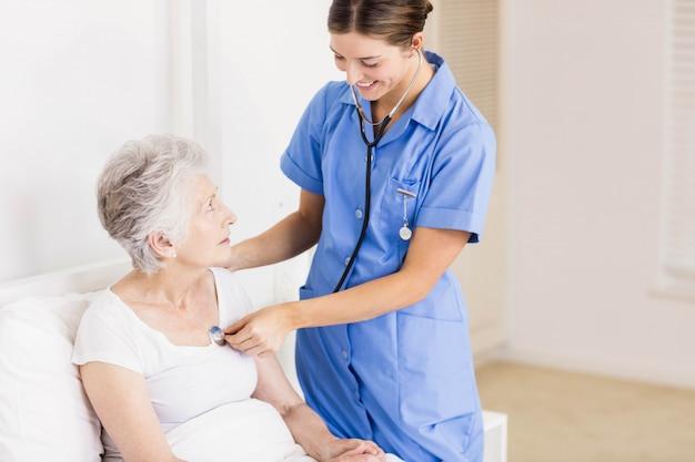 Doktor, der sich zu hause um leidendem älterem patienten kümmert