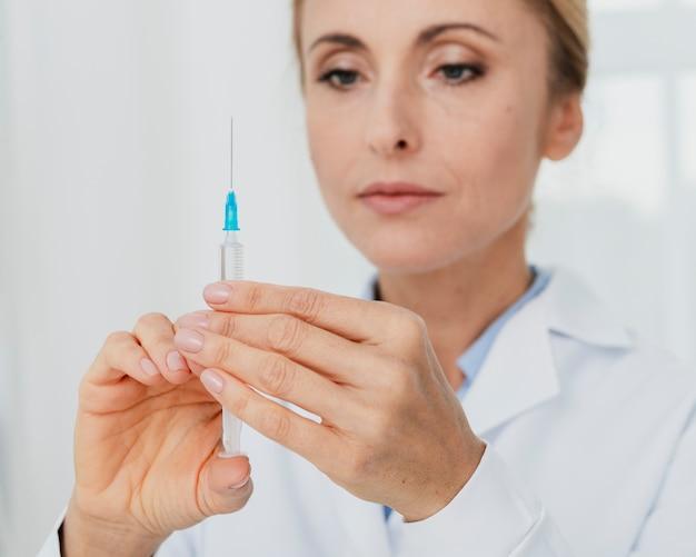 Doktor, der spritze für einspritzung vorbereitet