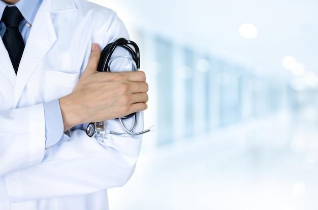 Doktor, der stethoskop am krankenhaus auf unscharfem blauem hintergrund hält