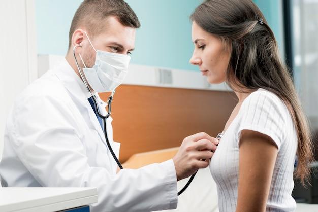 Doktor, der stethoskop auf patienten verwendet