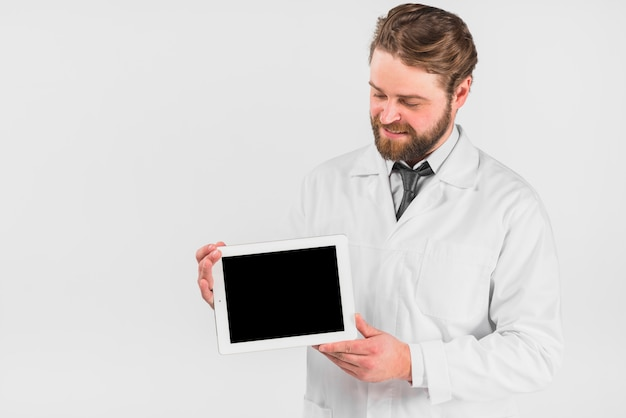 Doktor, der tablette hält und gerät betrachtet