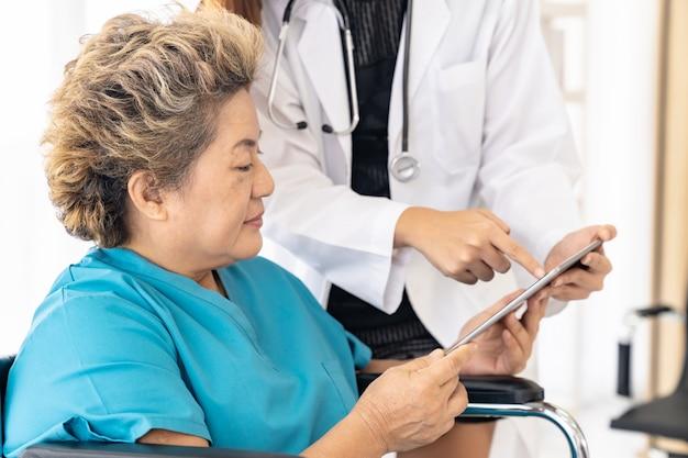 Doktor, der tablette mit altem patienten verwendet