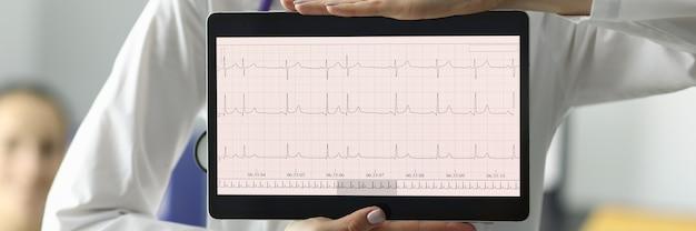 Doktor, der tablette mit elektrokardiogramm in der kliniknahaufnahme hält. konzept der diagnose von herzrhythmusstörungen