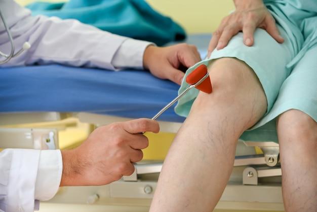 Doktor, der trigonalen kopf-neurologischen schlaghammer auf dem kniebereich verwendet.