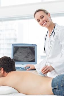 Doktor, der ultraschallscan an der rückseite des patienten durchführt