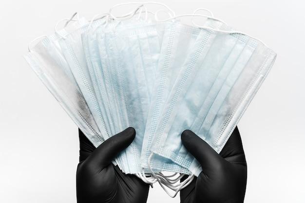 Doktor, der viele antibakterielle gesichtsmasken in zwei händen in schwarzen handschuhen auf weißem hintergrundkonzept hält