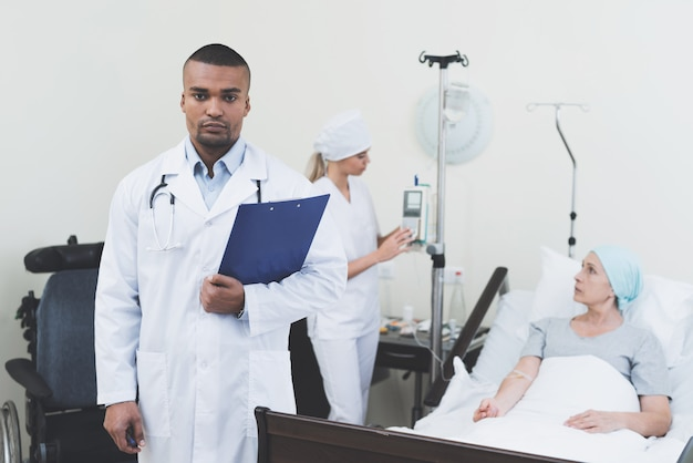 Doktor, der vor dem hintergrund des patienten aufwirft