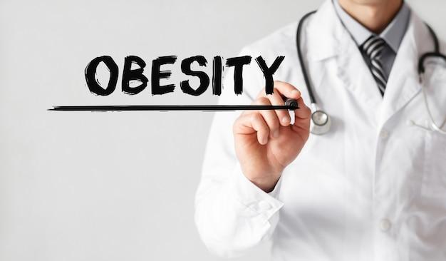 Doktor, der wort fettleibigkeit mit marker, medizinisches konzept schreibt