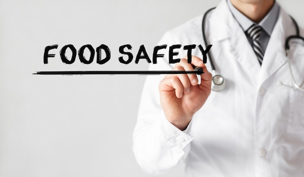 Doktor, der wort lebensmittelsicherheit mit marker, medizinisches konzept schreibt