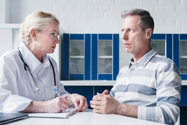 Doktor, der zu einem patienten neigt