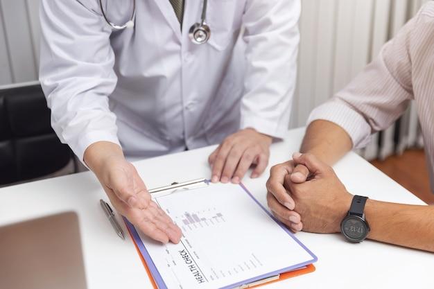 Doktor erklären symptome und medizinische behandlung zum patienten im krankenhaus