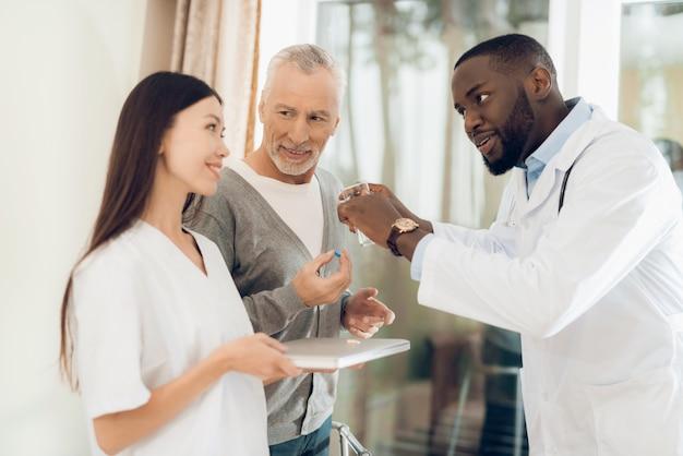 Doktor erklärt krankenschwester, wie eine patientin pillen nehmen sollte.