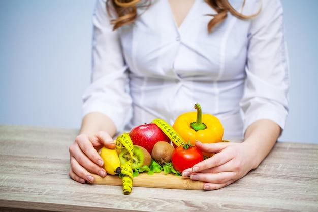 Doktor ernährungsberater, der frisches obst und gemüse für eine gesunde ernährung hält