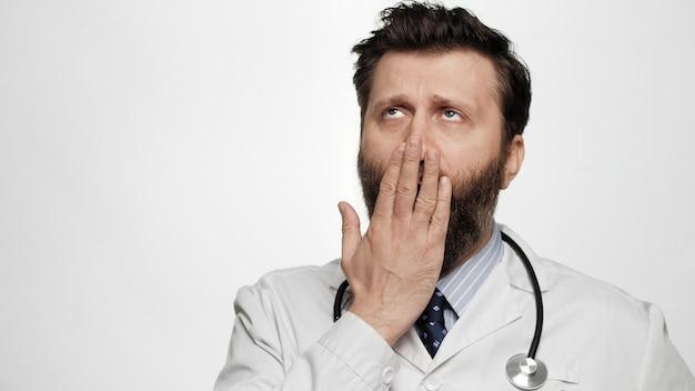 Doktor gähnt müder gelangweilter mann doktor auf weißem hintergrund gähnt und bedeckt seinen mund mit der hand
