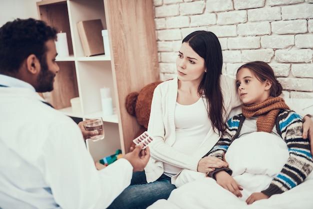 Doktor gibt pillen mit wasserpatienten im klinikraum.