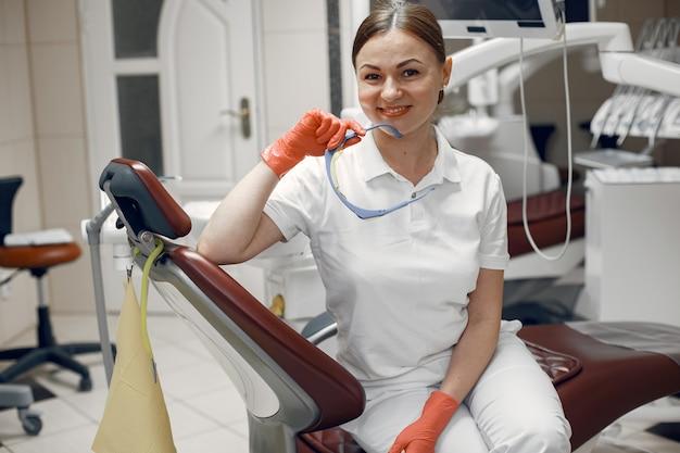 Doktor hält die brille. frau schaut in die kamera. zahnarzt wartet auf den patienten