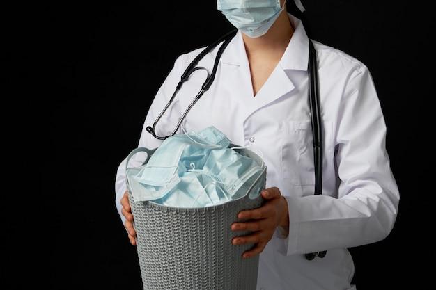 Doktor hält eimer voll mit gebrauchten gesichtsmasken und wirft sie als symbol für das ende der epidemie weg