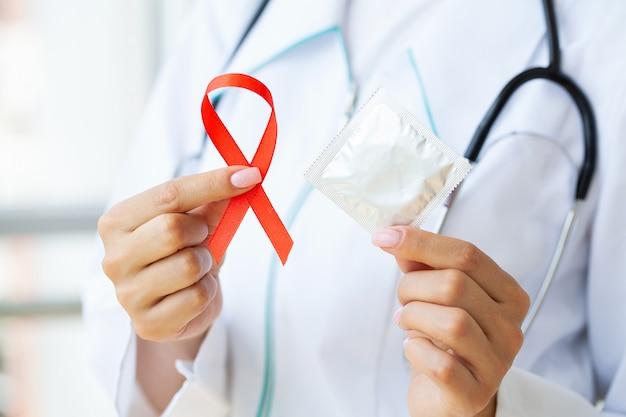 Doktor hält ein rotes band und ein kondom und fordert sicheren sex und schutz vor aids